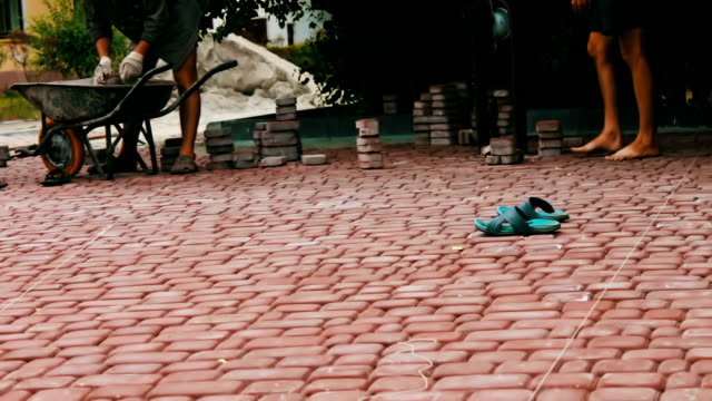 Men lay decorative multicolored paving tiles in a children's park.Repairing sidewalk. Worker laying stone paving slab. Laying colored tiles in city park. Hand fixed tessellated sidewalk tile video