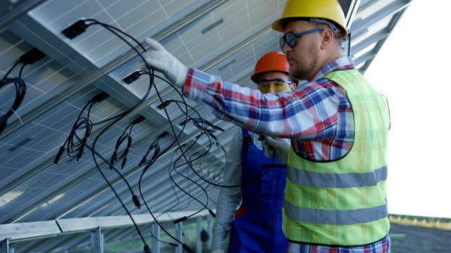 männer lernen, wie man solarzellen anschließen - bauarbeiterhelm stock-videos und b-roll-filmmaterial