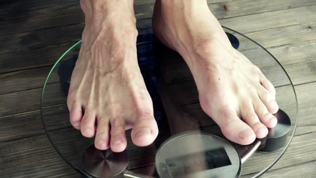 Men legs approaching to weighing digital instrument video