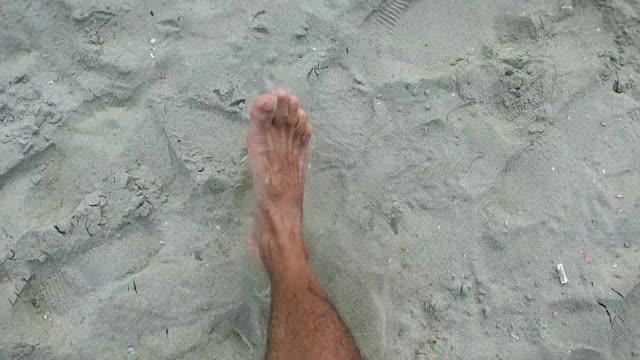 Men legs walking on a beach, slow motion video
