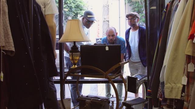 männer auf der suche im schaufenster der second-hand-shop - schaufenster stock-videos und b-roll-filmmaterial
