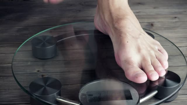 Men measuring weight on health scale. 3840X2160 UHD video video