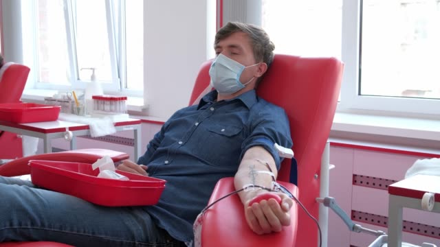 men on chairs wearing medical mask in blood donation center. donor giving blood. Covid 19 pandemic
