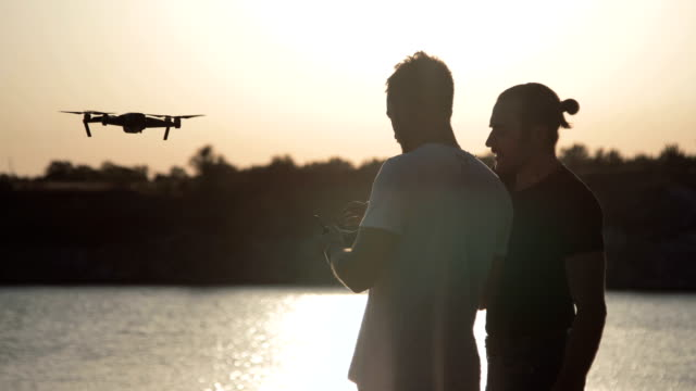Men on coast controlling drone video