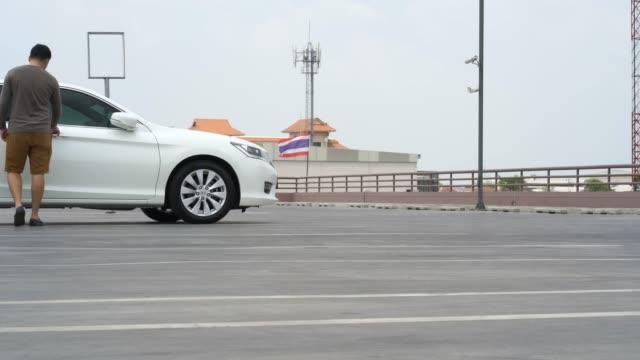 男性は駐車場で車のドアを開けます。 - 屋根点の映像素材/bロール