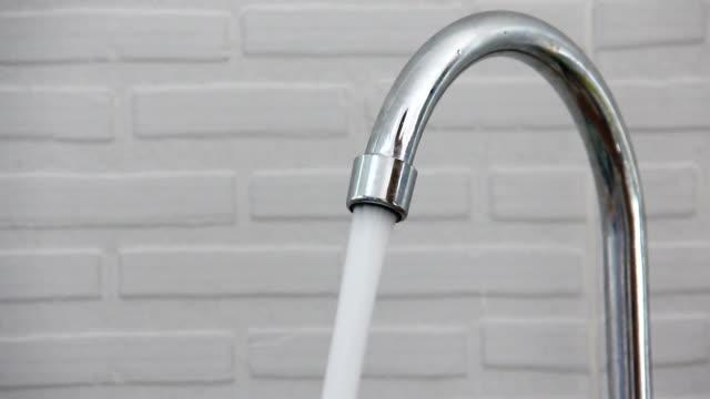 Men open wafer at valve of sink Men open wafer at valve of sink in kitchen room kitchen sink stock videos & royalty-free footage