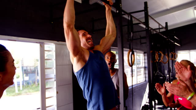 Men performing pull-up exercise while friends applauding him video