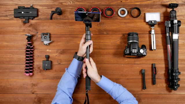Men photographer puts the phone on Selfie stick and shoot itself. Wooden table top view. Equipment for shooting on the table video