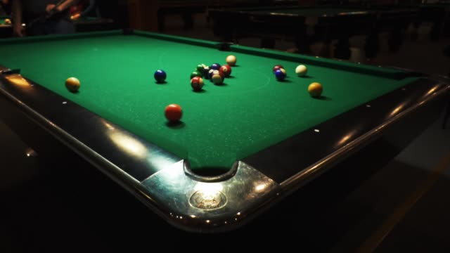 Men play billiards. The hand of a man takes the cue and hits the balls. Balls roll over the green table.