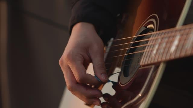 män spelar gitarr på stranden vid solnedgången, närbild. slow motion - akustisk gitarr bildbanksvideor och videomaterial från bakom kulisserna
