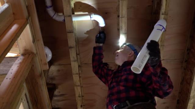 Men plumber glued plastic toilet white pipe in close up shot