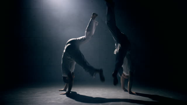 Men practicing capoeira Two men practicing capoeira in dark room. Slow motion martial arts stock videos & royalty-free footage