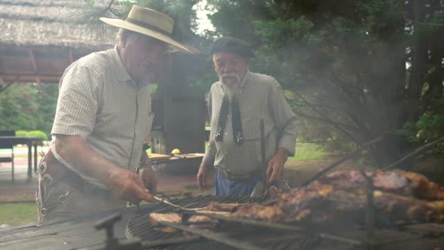 vidéos et rushes de hommes préparant le costillar pour la cuisson de bois de chauffage - argentine