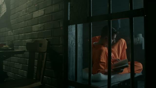 Men reading book in prison cell video