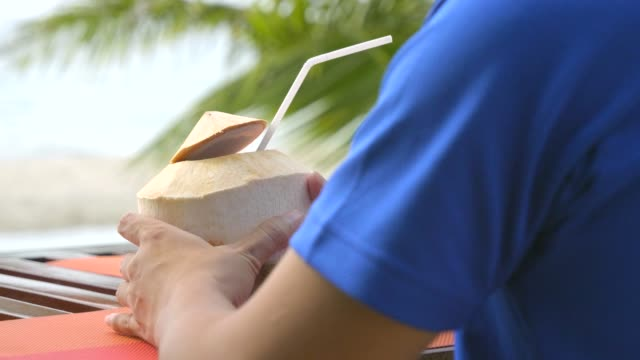 Men Relaxing at Beach on Chair with Drinking Coconut juice. 4K, Men Relaxing on Table and Chair with Drinking Coconut juice at Koh Chang Beach with the Beach and coconut palm tree background. Landmark Travel Beach and Island of Thailand. coconut palm tree stock videos & royalty-free footage