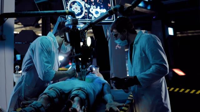 vidéos et rushes de les hommes scientifiques mènent une opération extraterrestre sur une station spatiale. fonctionne la surveillance de l'écran et d'autres appareils. - pratique médicale