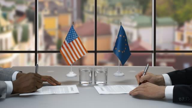 vídeos de stock e filmes b-roll de men signing papers at table. - afro americano