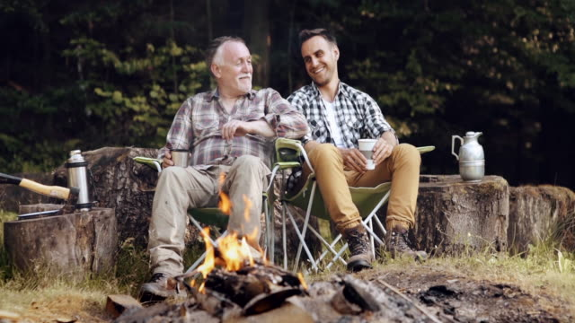 Men sitting and relaxing at bonfire