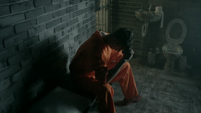 Men sitting on bed in prison cell video