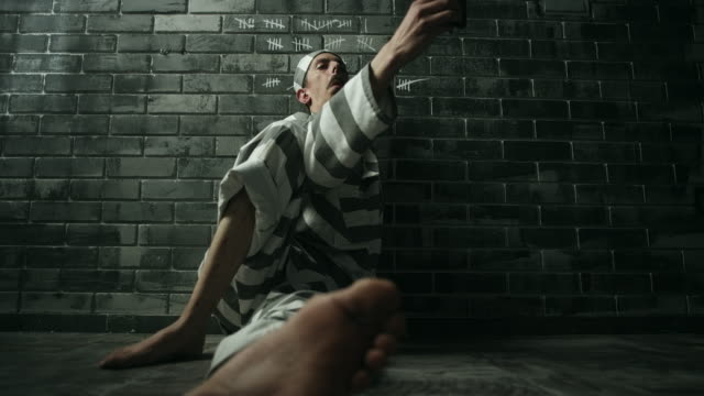 Men sitting on floor and taking selfies in prison cell video