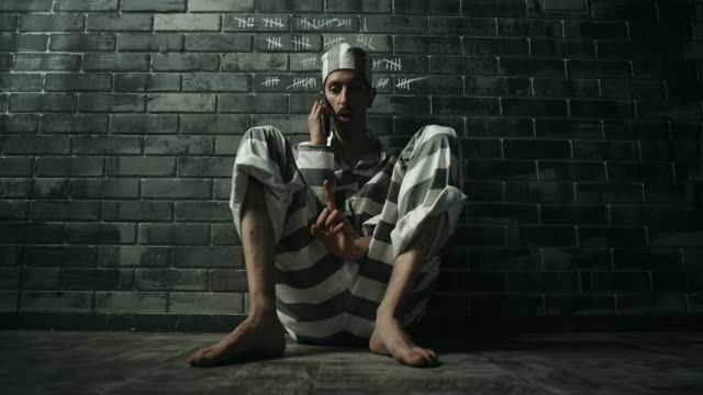Men sitting on floor and talking on phone in prison cell video