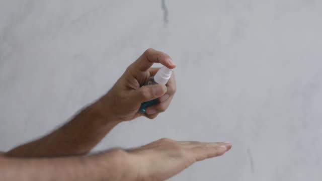 vídeos de stock, filmes e b-roll de homens pulverizam álcool nas mãos para evitar germes. - braço humano