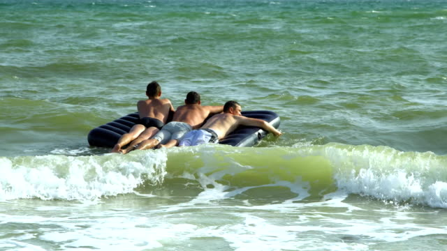 Men swim in the sea on an inflatable mattress. They are laughing. The mattress tosses on the waves. Slow motion. video