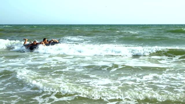 Men swim in the sea on an inflatable mattress. They are laughing. The mattress tosses on the waves. video