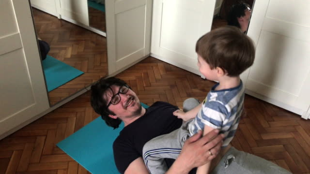 Men trying to do some exercises while his son is messing around