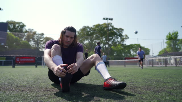 Men tying shoelace on soccer feild Mid adult men tying shoelace on soccer shoe while other teammates doing pre-game routine pre game stock videos & royalty-free footage
