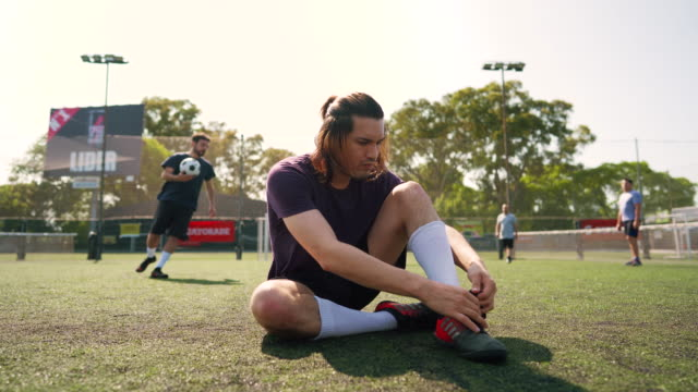 Men tying shoelace on soccer feild Mid adult men sitting on grass and tying shoelace on soccer shoe while other teammates doing pregame routine pre game stock videos & royalty-free footage