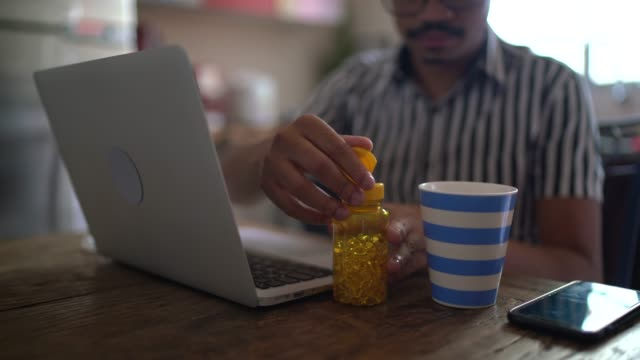 Men using laptop at home, blowing nose and taking medicine