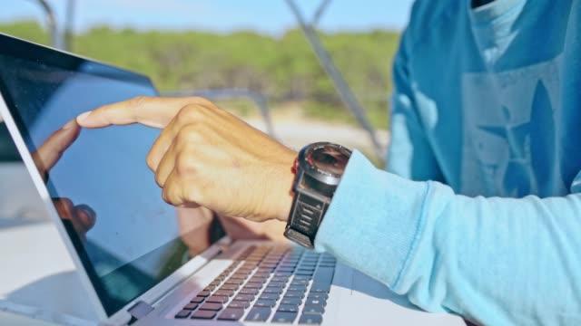 4k men using laptop on sunny sailboat, real time - rack focus video stock e b–roll