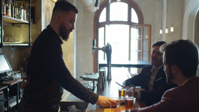 Men Using Phone to Make Contactless Payment for Beer in Bar - vídeo