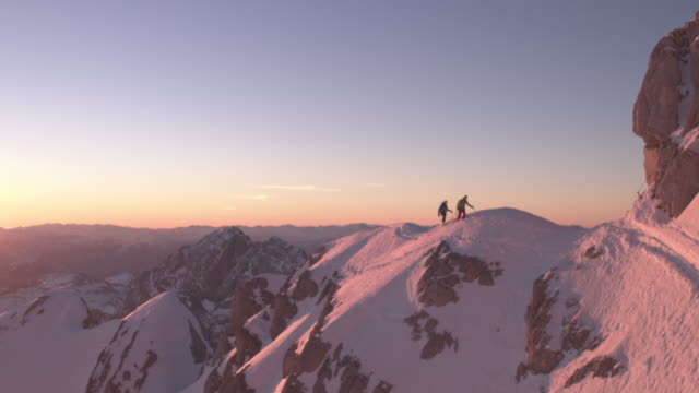 Men walking on snow covered ridge at sunrise Drone shot of male mountaineers walking on snow covered ridge. Mature men are hiking on snowcapped mountain during sunrise. They are on vacation. snowcapped mountain stock videos & royalty-free footage