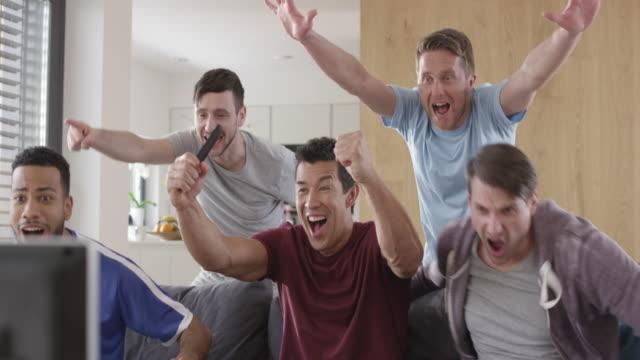 Men watching a football match and celebrating a goal
