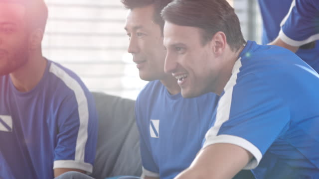men watching game on tv and celebrating a score - trykot filmów i materiałów b-roll