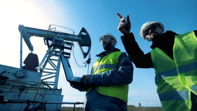 çalışan petrol derrick yakın bir laptop yürümek ile erkekler. fosil yakıt, petrol endüstrisi kavramı. - kule stok videoları ve detay görüntü çekimi