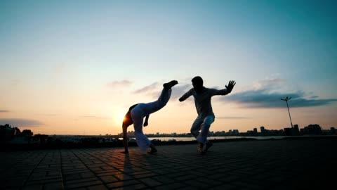 vidéos et rushes de hommes avec un physique de sportif sont engagés dans l'art martial brésilien capoeira en plein air, sur l'asphalte, sur le fond de la beauté de la promenade et le coucher du soleil de l'été - arts martiaux