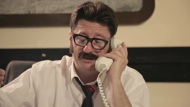 Men with mustaches and glasses smokes cigarette, talking on a retro phone, while sitting on a desk