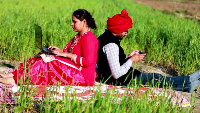Men & women portrait in the green field using laptop & Smartphone video