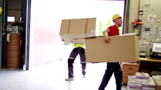 Men working at a warehouse. Carrying heavy boxes Distribution warehouse. Male workers in protective workwear and helmets occupational safety and health stock videos & royalty-free footage