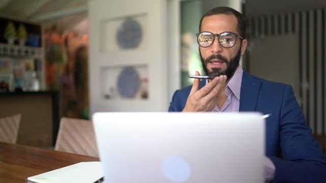 vídeos y material grabado en eventos de stock de hombres trabajando desde casa, enviando mensajes de voz en el teléfono inteligente - financial planning