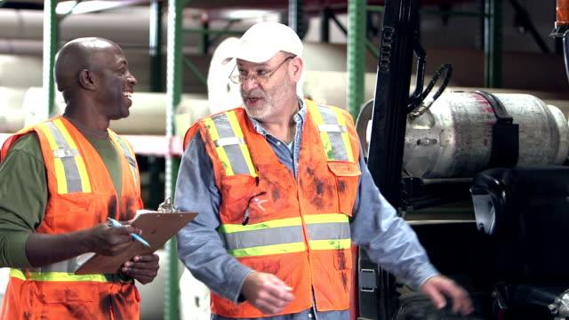 män som arbetar i mattan lager talar, gaffeltruck - kroppsarbetare bildbanksvideor och videomaterial från bakom kulisserna