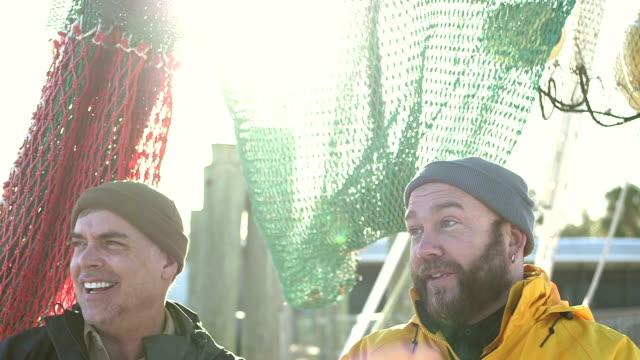 men working on commercial fishing boat conversing - rybak filmów i materiałów b-roll