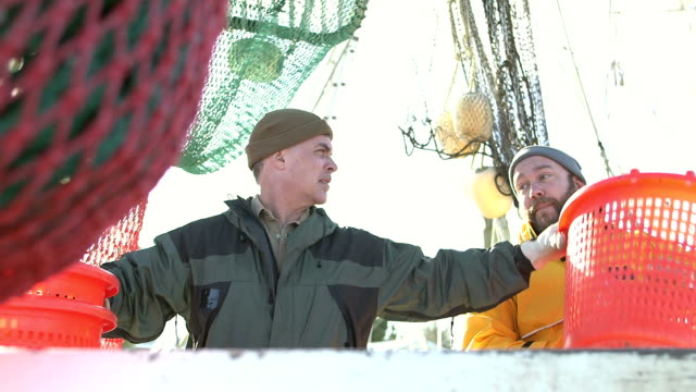 Men working on commercial fishing boat Two mature men working together on the deck of a commercial fishing trawler or shrimp boat, nets hanging behind them, conversing as they stack empty baskets for holding their catch. recreational boat stock videos & royalty-free footage