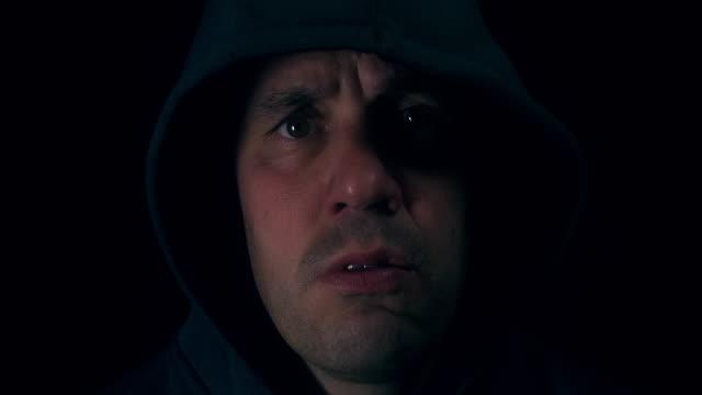 Menacing looking male looking threatening in hoodie video