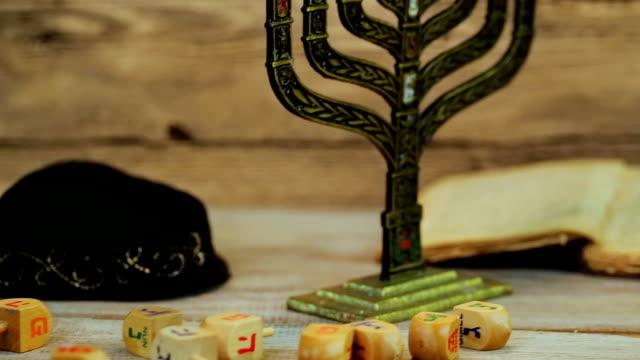 Menorah with candles for Hanukkah against defocused lights, video