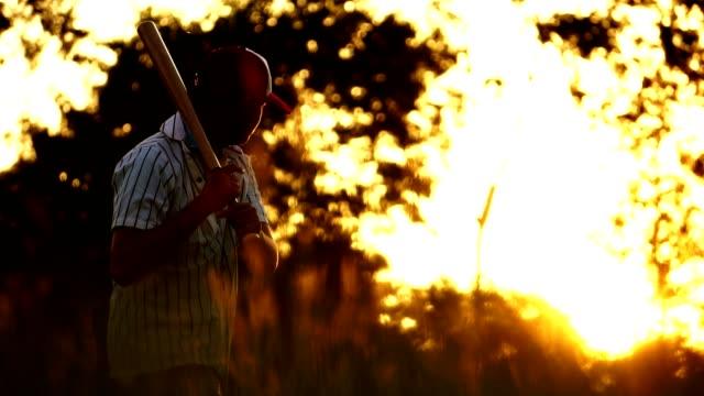 Men's baseball practice hitting a baseball with the light of sunset video