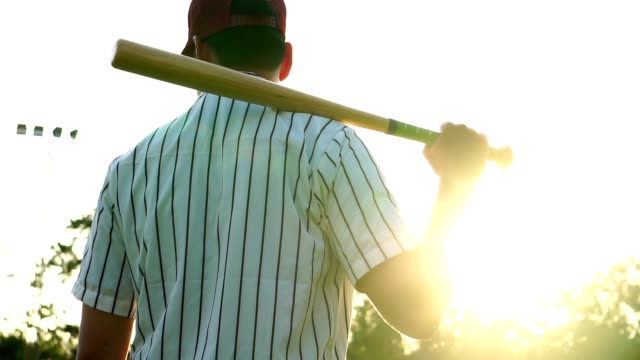 Men's baseball practice hitting a baseball with the light of sunset video